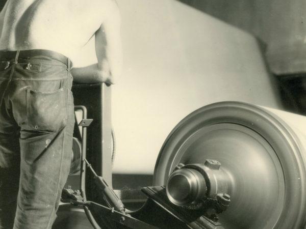 Shirtless employee working a calendar machine inside the Newton Falls Paper Mill in Newton Falls