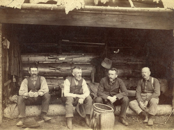 Four hunting guides in an Adirondack lean-to in Cranberry Lake