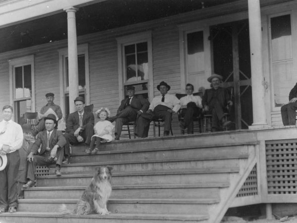 Paper plant employees and family members sit on the porch of a hotel in Pyrites