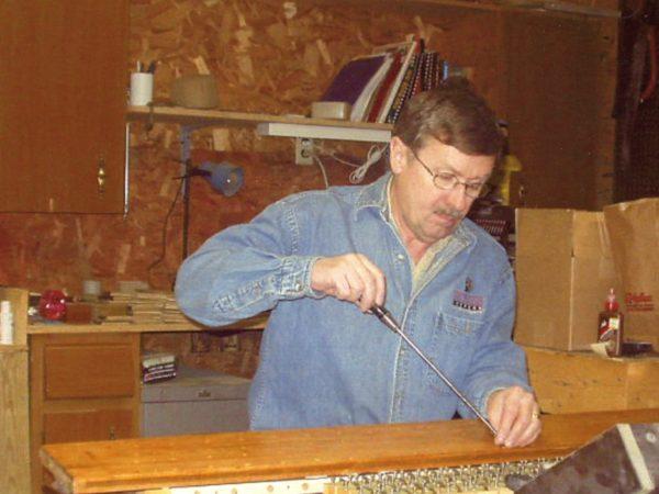 Wayne Lincoln repairing player piano in Massena