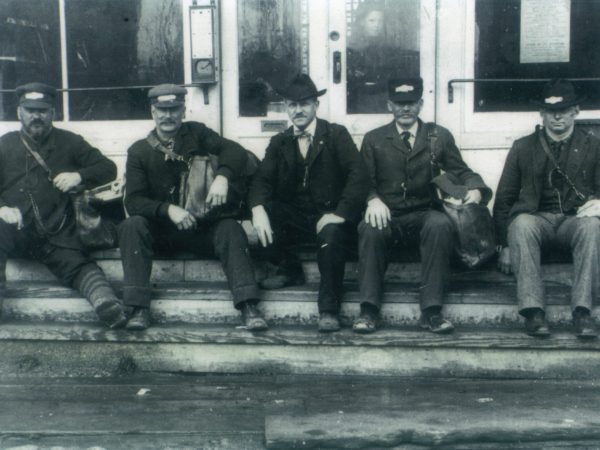 Five postmen sit on the steps of Post Office in Lisbon