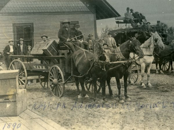 Stagecoach and station wagon parked outside station on the Northern Adirondack Railroad from Moira to Tupper Lake