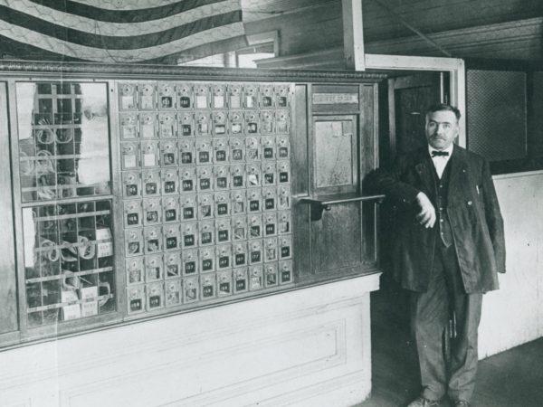 Postmaster inside the post office in De Kalb Junction