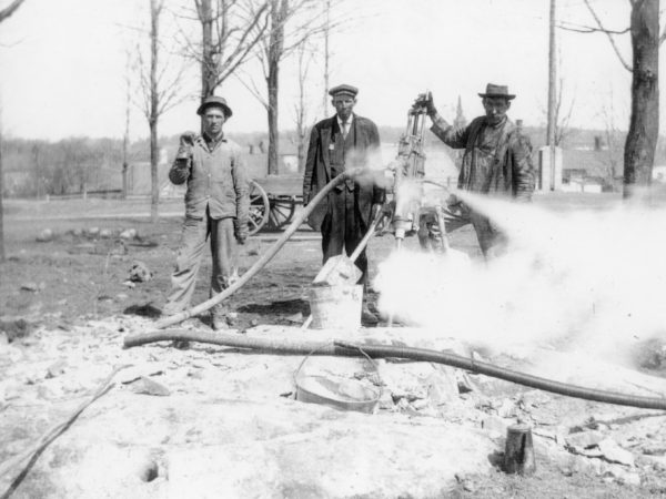Three workers from the town road crew using a steam drill on school hill. 1910. De Kalb Junction, NY. Photograph by Robert Woodward.