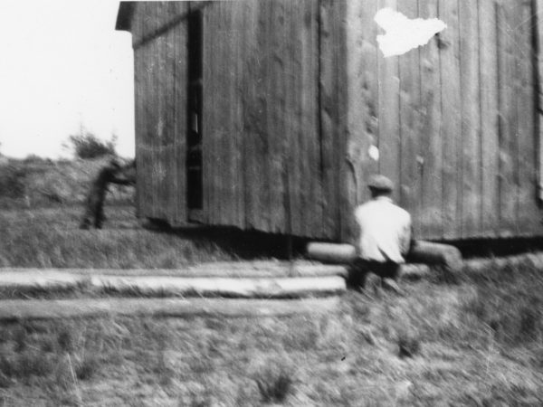 Moving a barn on wooden rollers in the Town of De Kalb