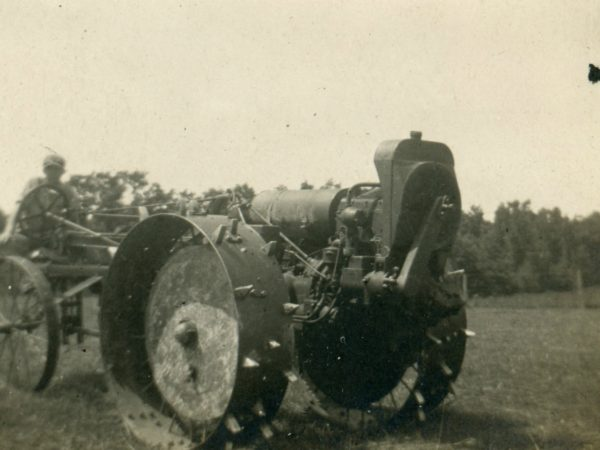 Driving an early Moline tractor in the Town of De Kalb
