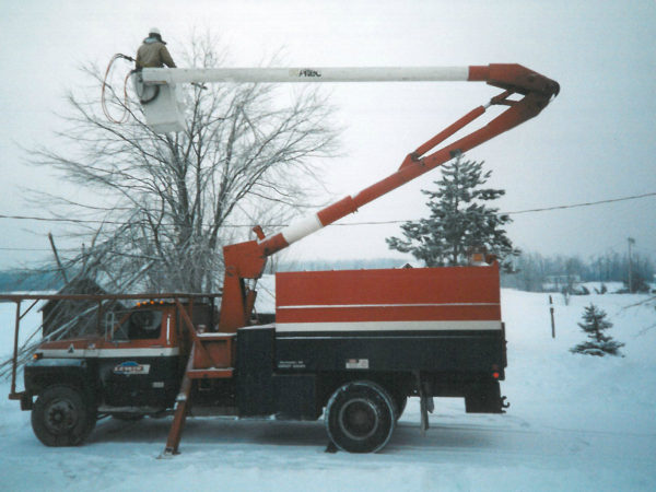 Cutting branches hanging on a power line after 1998 ice storm in Canton