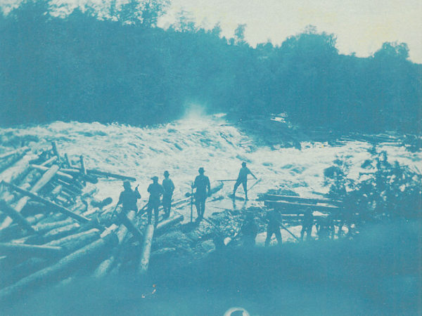 Loggers stand on the banks of the Racquette River during a log drive in Colton