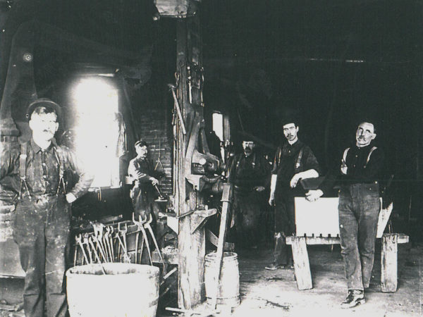 Workers inside Henry Jones General Blacksmith and Machine Shop in Richville