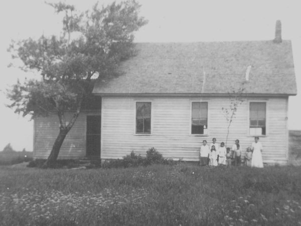 Teacher with her students in front of the Warren School in De Peyster