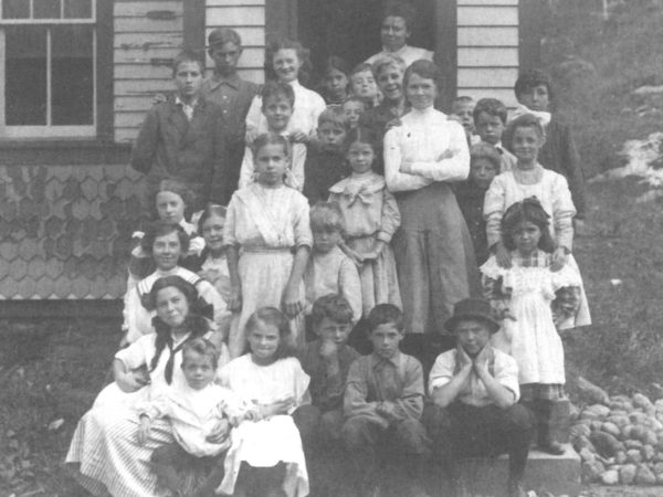 Schoolchildren and their teacher in front of the Star Lake School in Oswegatchie