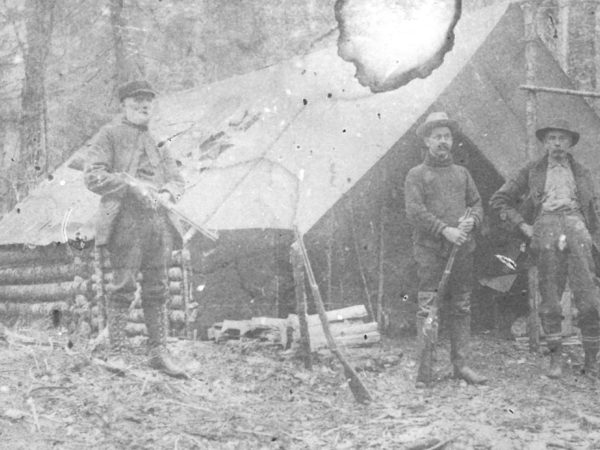Hunters outside a hunting camp in Fine