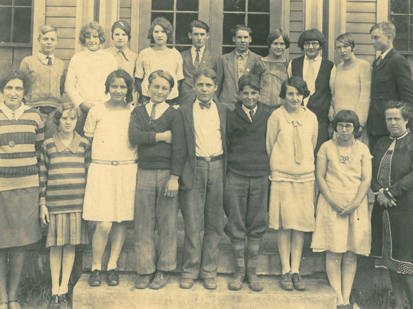 Students and two teachers at the entrance of the Oswegatchie Union School in Star Lake