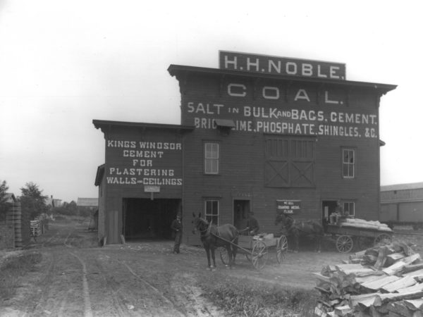 Men with horses and wagons in front of H.H. Noble Coal in Gouverneur