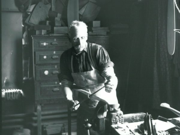 Nelson Brown shapes a boat piece in his shop in Rushton Boat works
