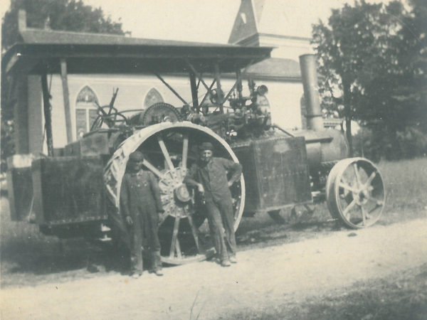 Traction steam engine in front of a church in Saint Lawrence County