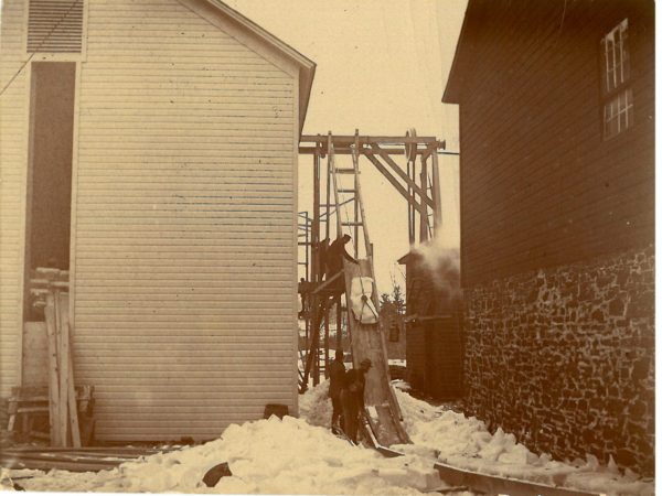 Men moving ice using ropes into ice house in Canton
