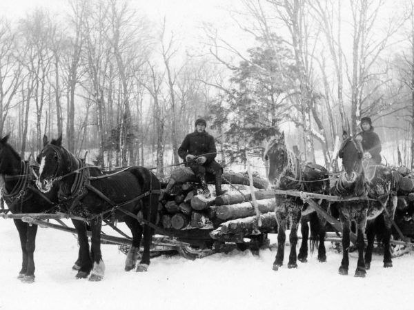 Two men driving log sleds in Hermon