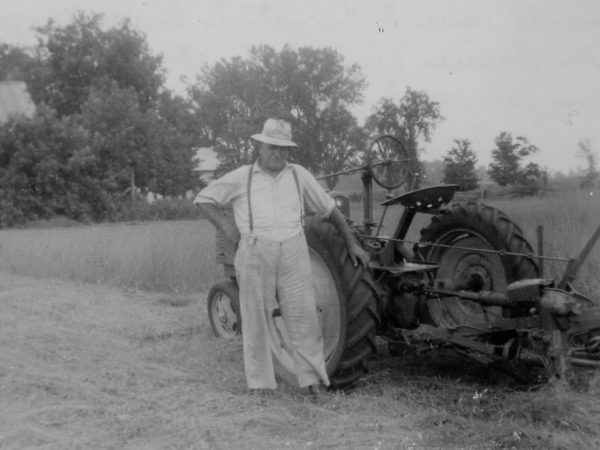 Frank Squire using John Deere tractor to cut hay in Hopkinton