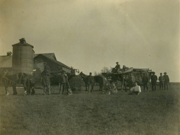 Work crew posing with threshing equipment in Hermon