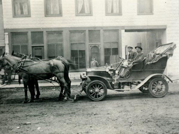 Horse team towing an early automobile on Church Street in downtown Hermon