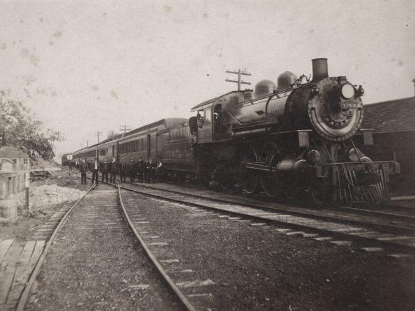 Eleven man crew in front of a passenger train in De Kalb