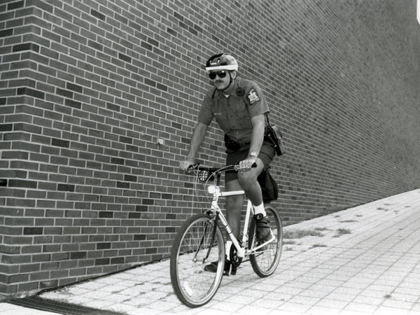 Campus security officer riding a bicycle at SUNY Potsdam in