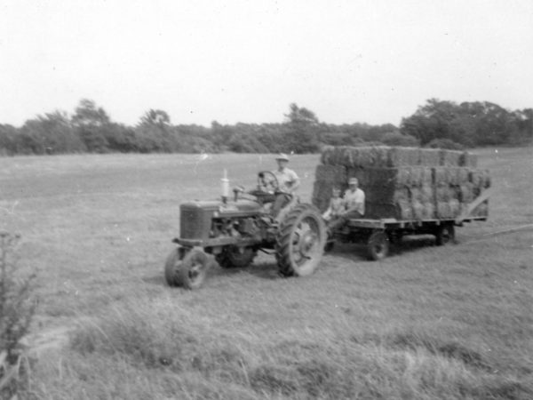 Moving hay bales with a Farmall tractor in Hammond