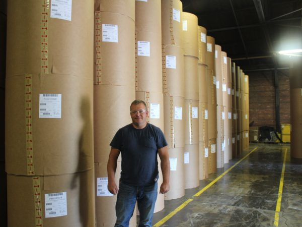 Worker in front of packaged paper rolls in Potsdam