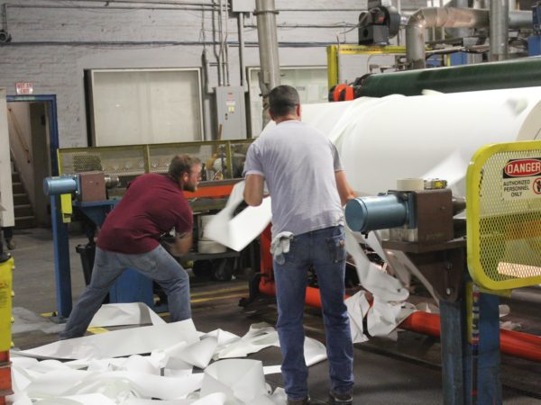 Men make rolls of paper in the Potsdam Specialty Paper Company in Potsdam