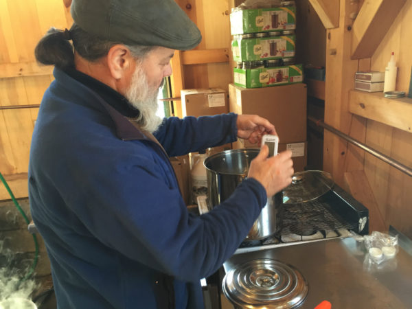 Michael Greer finishes his maple syrup on a gas stove in Potsdam