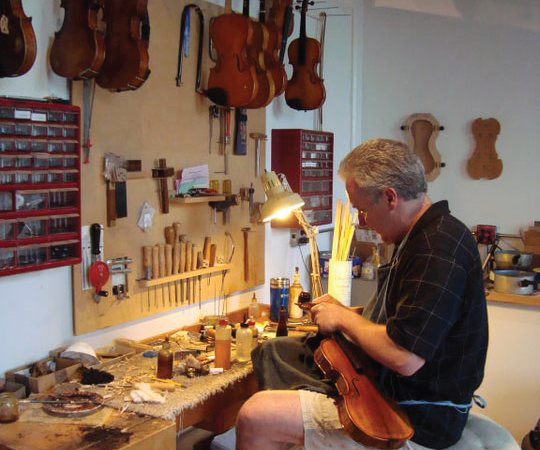 Dustin Saam crafting a violin at The Shirt Factory in Glens Falls