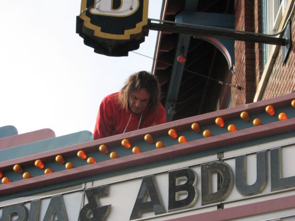 Bob Card works on the marquee of The Strand theater in Old Forge