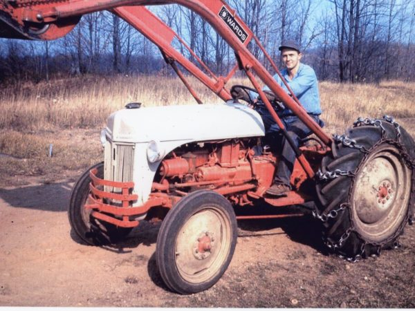 Ross Young on a bulldozer used for logging in Harrisville