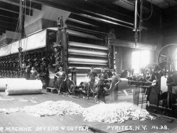 Men with paper machines inside the DeGrasse River Paper Company in Pyrites