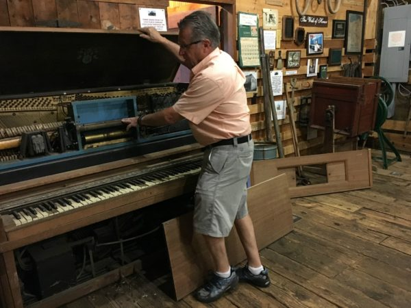 Wayne Lincoln restoring a player piano in Lisbon