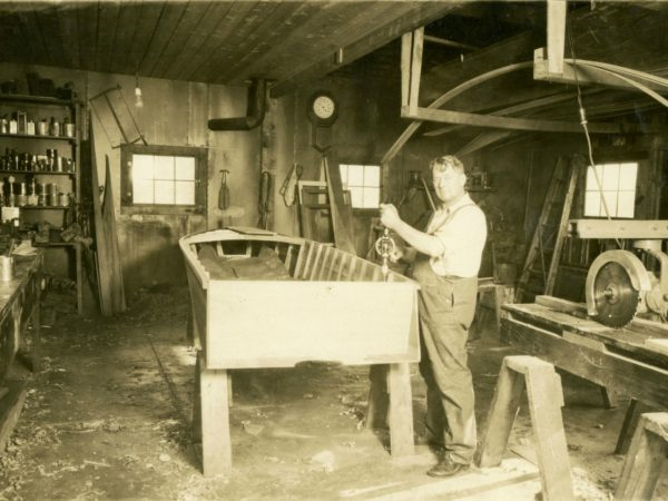 Charles Hanmer working on a boat in Long Lake