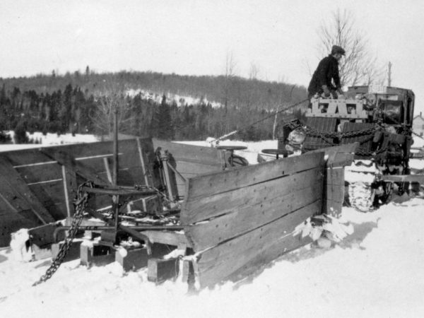 Man atop a wooden snow plow in Long Lake