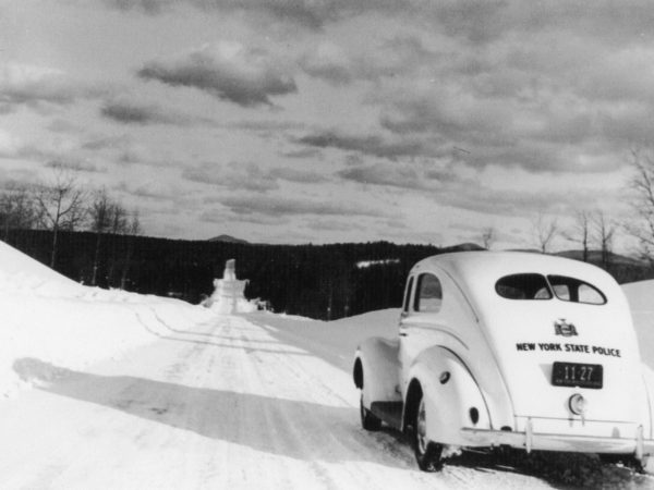 New York State Trooper automobile on snowy road in Long Lake
