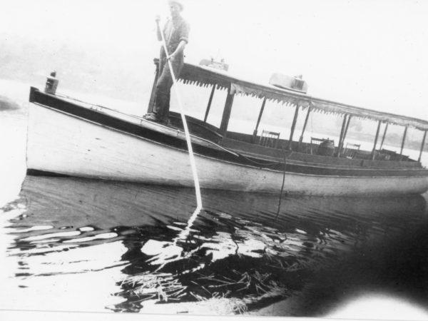 Man rows a pleasure boat in Long Lake