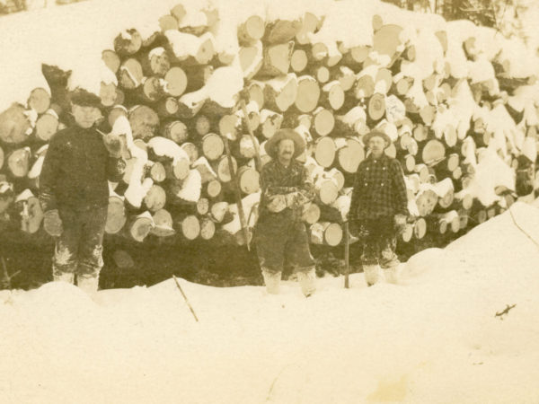 Loggers pose in front of snowcapped log pile in Long Lake