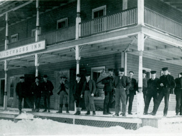 Men on the porch of the Wilderness Hotel in Sabattis