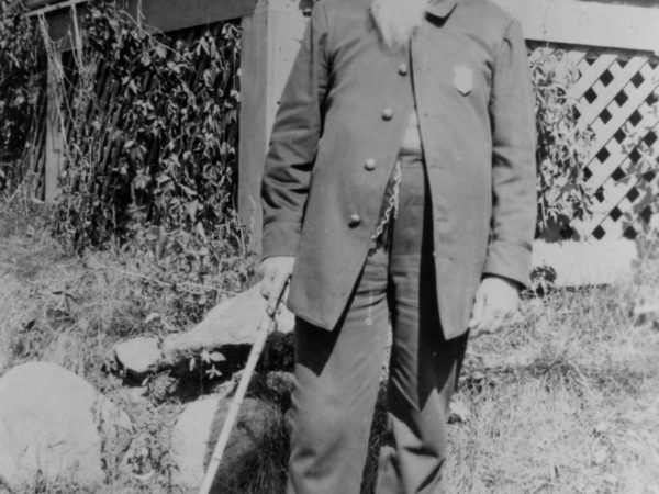 Charles Bailey Hanmer in front of a porch in Long Lake