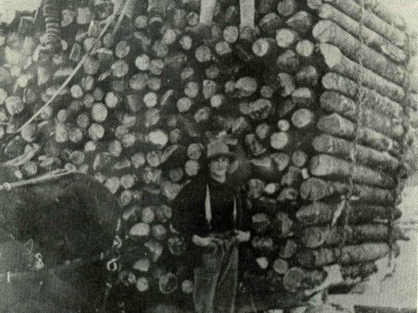 Two men on top of a sleigh load of logs on Long Lake