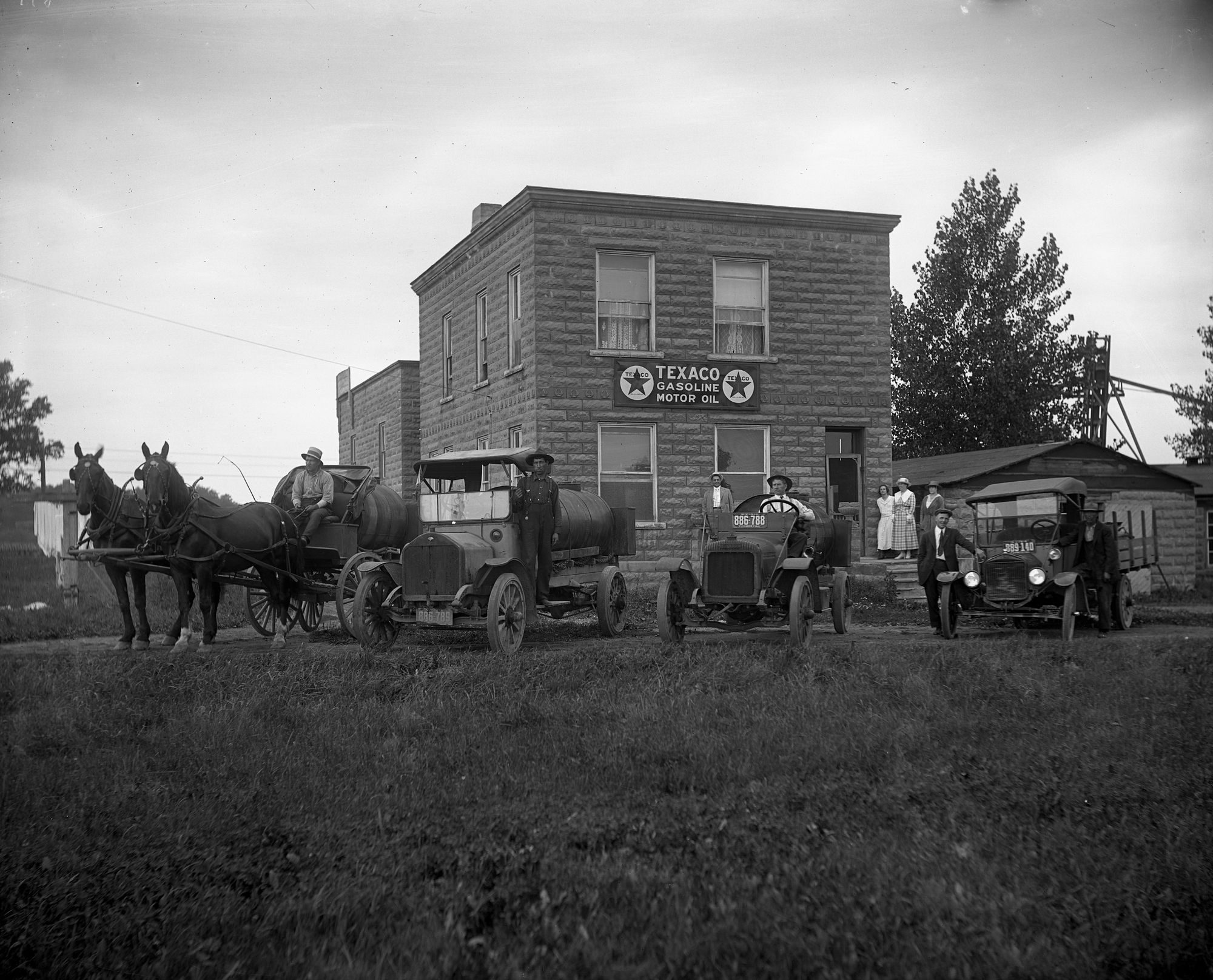 Horse drawn wagons and automobiles at Texaco Station in