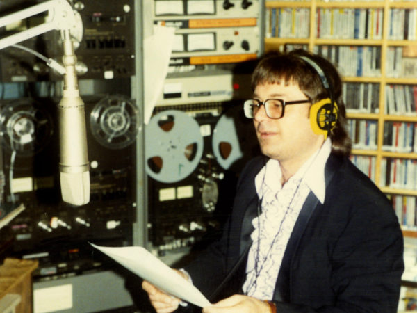 NCPR announcer Peter Euler reads into microphone at studio in Canton