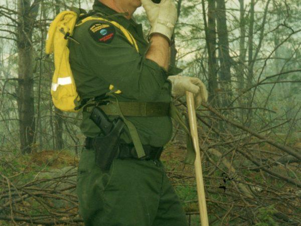 Forest ranger speaks into a walkie-talkie in Rossie
