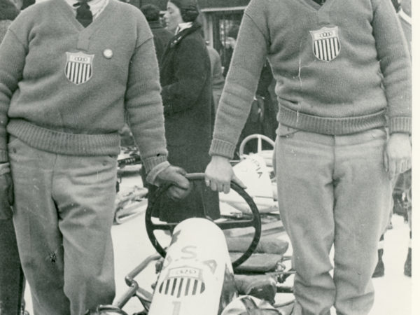 Olympic athletes posing with their bobsled