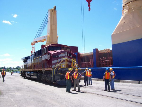 Stevadores loading locomotive onto ship at the Port of Ogdensburg