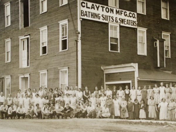 Workers pose outside the Clayton Manufacturing Company in Clayton